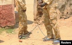 FILE - South Sudanese soldiers suspected of beating and raping civilians are chained together at the presidential guard unit, within the Sudan People's Liberation Army headquarters, after their arrest in Juba, March 3, 2017.