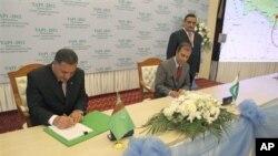 Kepala perusahaan energi Turkmenistan Sahatmurad Mamedov (kiri) dan perwakilan dari Pakistan Mobin Saulat menandatangani dokumen pembangunan jaringn pipa di Avaza, Turkmenistan (23/5)