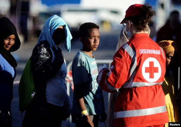 Migrants stand in a line in front of Red Cross member after disembarking from the Italian navy ship Borsini in the Sicilian harbor of Palermo, southern Italy, July 20, 2016.