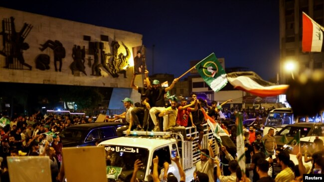 Iraqi supporters of Sadr's movement celebrate preliminary results of parliamentary elections in Baghdad, Iraq, October 11, 2021.