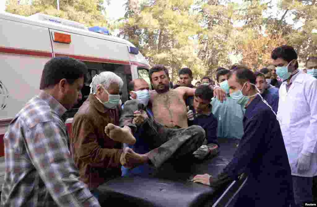 Residents and medics transport a Syrian Army soldier, wounded in what they said was a chemical weapon attack near Aleppo, March 19, 2013.