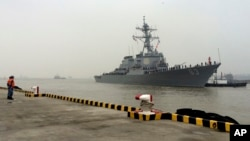FILE - Chinese Navy personnel stand guard as guided missile destroyer USS Stethem arrives at the Shanghai International Passenger Quay for a scheduled port visit in Shanghai, China, Nov. 16, 2015.