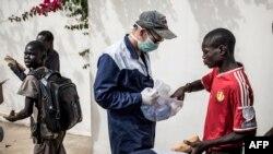 Un travailleur du Village Pilote distribue de l'eau et des sandwichs aux enfants des rues de Dakar, le 10 avril 2020.