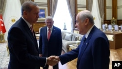 Turkey's President Recep Tayyip Erdogan, left, greets Devlet Bahceli before a meeting in Ankara, Turkey, July 25, 2016. Erdogan met Monday with leaders of the main opposition parties, Republican People's Party leader Kemal Kilicdaroglu, National Movement Party leader Devlet Bahceli and Turkish Prime Minister Binali Yildirim.