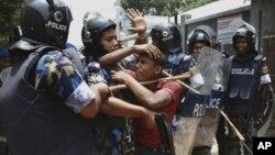 Polisi Bangladesh menahan seorang pekerja tekstil dalam unjuk rasa menuntut kenaikan upah di Dhaka, Bangladesh (foto: dok). Upah pekerja tekstil di Bangladesh termasuk salah satu yang terendah di dunia.