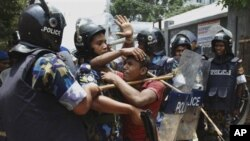 Bangladeshi policemen detain a garment worker during a protest in Ashulia, Dhaka, Bangladesh, Thursday, June 14, 2012. The workers were staging a demonstration demanding a raise in wages. (AP Photo/Shahadat Parvez)