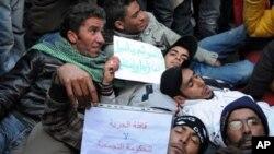 ژمارهیهک خۆپـیشـاندهری تونسی له بهردهم ئۆفیسی سهرهک وهزیری وڵاتهکهیان مانیان گرتووه، دووشهممه 24 ی یهکی 2011