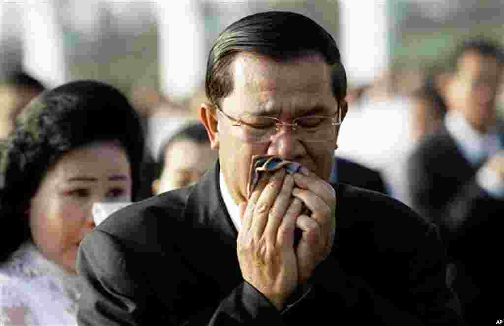 Cambodian Prime Minister Hun Sen and his wife Bun Rany cry during a memorial service near a bridge where festival goers were killed Monday in a stampede in Phnom Penh, Cambodia, Thursday, Nov. 25, 2010. (AP Photo/Sakchai Lalit)