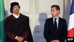 Le président français Nicolas Sarkozy (R) et le leader libyen Mouammar Kadhafi posent lors de la signature de 10 milliards d'euros de contrats commerciaux, à Paris, le 10 décembre 2007.