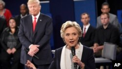 Kandidat presiden AS dari Partai Demokrat Hillary Clinton berbicara dalam debat kepresidenan disaksikan oleh lawannya dari Partai Republik, Donald Trump, di Washington University, St. Louis (9/10).