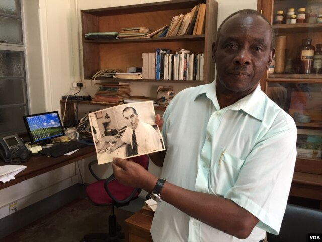 Louis Mukwaya, a mosquito researcher at the Uganda Virus Research Institute near Entebbe, displays a photograph of a Scottish medical entomologist. Alexander Haddow led the research team responsible for isolating the Zika virus in 1947. (J. Craig/VOA)