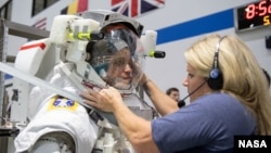 In this May 22, 2019, photo, 2017 NASA astronaut candidate Jessica Watkins is helped into a spacesuit prior to underwater spacewalk training at NASA Johnson Space Center's Neutral Buoyancy Laboratory in Houston. Photo Credit: (NASA/David DeHoyos)