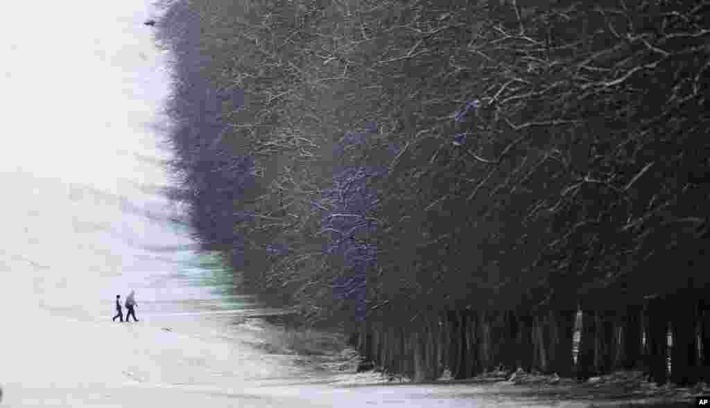 Dua orang berjalan di lapangan yang dipenuhi salju di Stormont, Belfast, Irlandia utara.