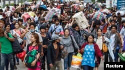 Cambodian migrant workers carry their belongings as they walk to cross the border at Aranyaprathet in Sa Kaew, June 15, 2014.