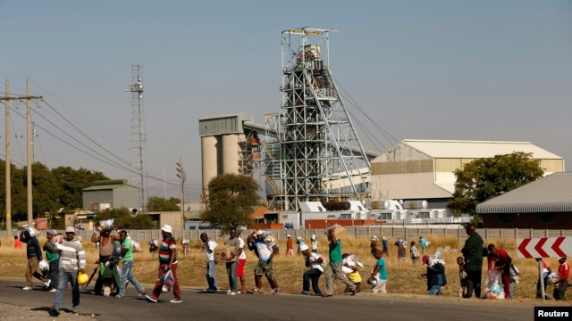 Members of the mining community carry food parcels donated by an Aid organisation, Gift of the Givers, at the Khomanani mine in Rustenburg, South Africa, May 28, 2014.