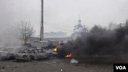 Xe cộ bốc cháy trên đường phố sau một vụ pháo kích của phiến quân thân Nga vào khu vực dân cư ở Mariupol, miền đông Ukraine, ngày 24/1/2015.