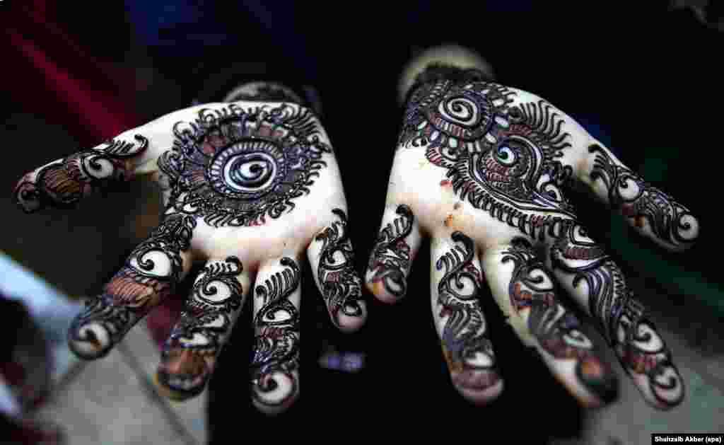 ក្មេងស្រីម្នាក់សម្ងួតស្នាមសាក់ Henna នៅលើដៃរបស់នាង មុនពេលពិធីបុណ្យ Eid al-Fitr នៃសាសនាមូស្លីម ដើម្បីកំណត់នូវការបញ្ចប់ពិធីបុណ្យរ៉ាម៉ាឌន ក្នុងក្រុងការ៉ាឈី ប្រទេសប៉ាគីស្ថានកាលពីថ្ងៃទី០៥ ខែកក្កដា ឆ្នាំ២០១៦។