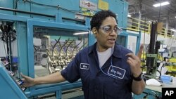 Gina Johnson performs leak tests on hydraulic fittings at the Eaton Corp. plant in Berea, Ohio, January 25, 2012.