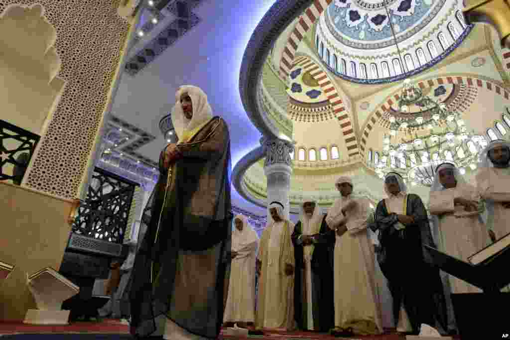 An Emirati Imam, left, leads Eid Al-Adha prayers at Farooq Omar Inb Al Khatab mosque in Dubai, United Arab Emirates, October 26, 2012.