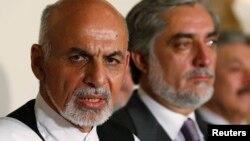 2014年7月12日阿富汗总统候选人阿什拉夫·加尼(左)与竞选对手阿卜杜拉·阿卜杜拉(右)在喀布尔新闻发布会