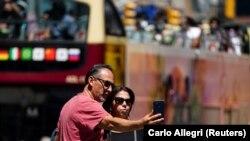 Du khách chụp ảnh tại Times Square, New York, ngày 14/5/2021 sau hướng dẫn mới của Trung tâm Kiểm soát và Phòng ngừa Dịch bệnh Mỹ (CDC) cho phép những người đã tiêm chủng khỏi mang khẩu trang.