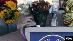 Seorang perempuan meletakkan karangan bunga di luar kantor Anggota Kongres Gabrielle Giffords di Tucson, Arizona, Sabtu, 8 Januari.