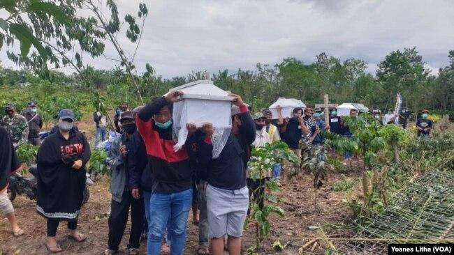 Warga mengusung empat peti mati menuju pekuburan Desa Kalemago, Kecamatan Lore Timur, Kabupaten Poso, Sulawesi Tengah. Rabu (12/5/2021) Foto : Yoanes Litha