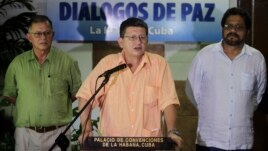 Revolutionary Armed Forces of Colombia (FARC) negotiator Pablo Catatumbo (C) reads a document as FARC lead negotiator Ivan Marquez (R) and FARC negotiator Ricardo Tellez listen in Havana, Aug. 23, 2013.