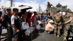 21일 필리핀 재해 복구를 위해 파병된 미 해군들이 타클로반시의 태풍 피해 주민들에게 식수를 나눠주고 있다.