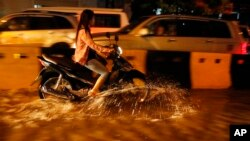 A Cambodian motorist rides a scooter through a street flooded by heavy rain fall in Phnom Penh, Cambodia, Friday, July 31, 2015. (AP Photo/Heng Sinith)