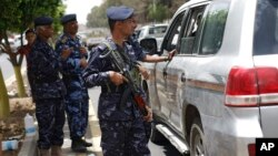 Policemen check a car at a checkpoint on a street leading to the Yemeni Interior Ministry in Sanaa, Yemen, Aug. 23, 2014.