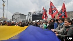 Protesters wave a giant Ukrainian flag during a protest rally in Kiev on June 5, 2012.