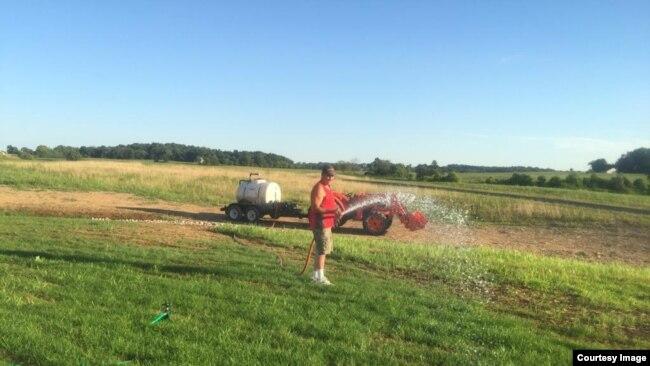 Danny Filsinger, suami Supadmi, menyirami rumput dengan semprotan air.