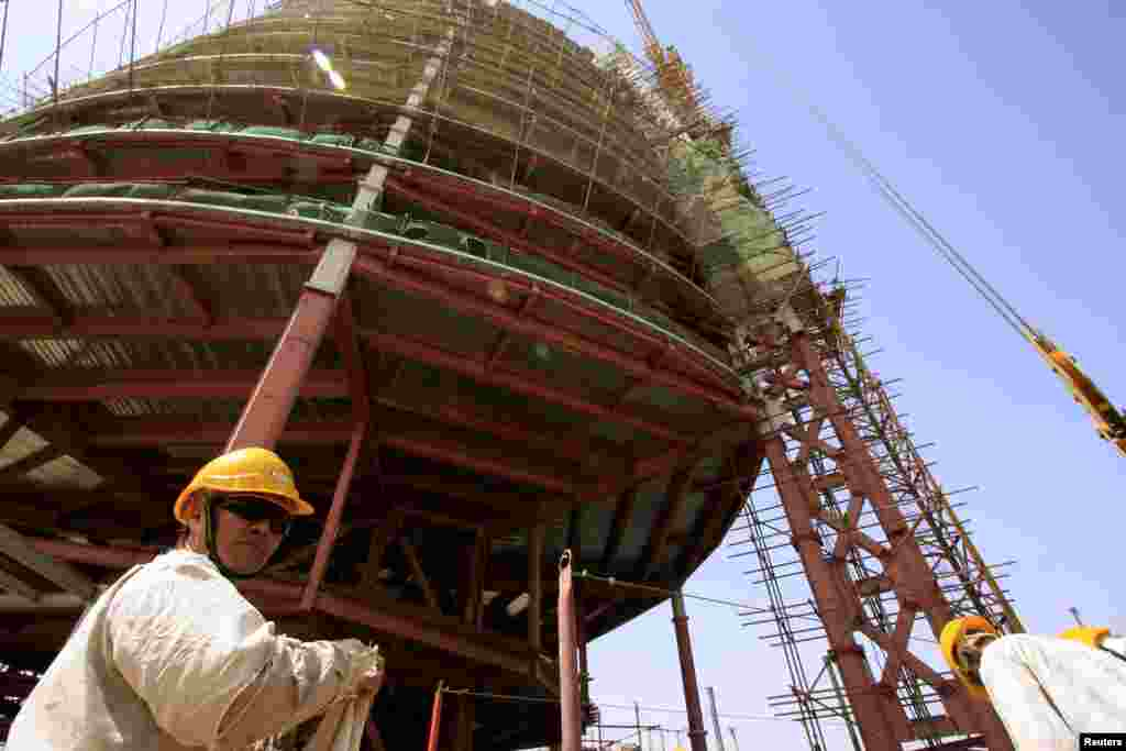 A building rises behind a Chinese engineer on the skyline of Khartoum, the capital of Sudan in 2009.