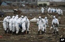 មន្រ្តីប៉ូលីសជប៉ុនមួយក្រុមពាក់សម្លៀកបំពាក់ព៌ណសដើម្បីការពារសារជាតិរ៉េអាក់ទ័រ លើកជនរងគ្រោះម្នាក់ ខណៈដែលមួយក្រុមទៀតលើកសាកសពនៅខាងក្រោយ ក្នុងពេលស្វែងរកមនុស្សដែលបាត់ខ្លួននៅ Minami Soma នៅ Fukushima Prefecture នៅប្រទេសជប៉ុន កាលពីថ្ងៃទី៨