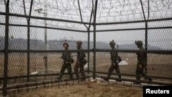 South Korean soldiers patrol along a barbed-wire fence, near the demilitarized zone (DMZ) which separates the two Koreas in Paju, north of Seoul, April 5, 2013.