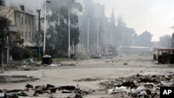 FILE - In this photo released by the Syrian official news agency SANA, damaged and blocked street where clashes erupted between the Syrian government forces and rebels, near the Abbassiyin square, east Damascus, Syria, March 20, 2017.