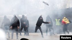 Para pendukung kellompok sayap kanan melemparkan sesuatu ke udara, saat berlangsungnya aksi protes menentang kesepakatan PBB soal migrasi global (Marrakesh Migration Pact) di Brussels, Belgia, 16 Desember 2018.