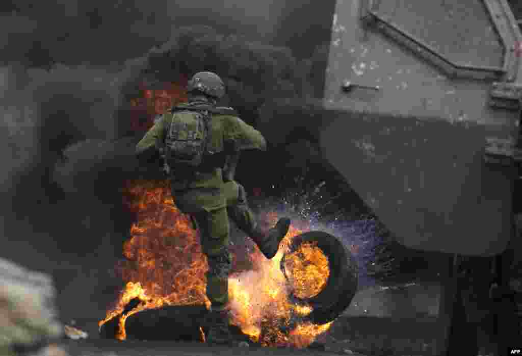 An Israeli soldier removes burning tires from the road during clashes with Palestinian protesters following a demonstration against the expropriation of Palestinian land by Israel in the village of Kfar Qaddum, near Nablus in the occupied West Bank.