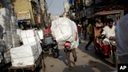 An Indian labourer carries a load through a busy street on a hot afternoon in New Delhi, India, Friday, May 13, 2016.