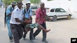 Binh sĩ Somalia đưa những người bị thương, trong vụ tấn công tại khuôn viên tòa án ở Mogadishu, đi cứu chữa, 14/4/13