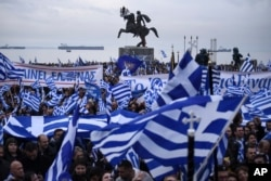 "FILE - Greek protesters wave flags and banners during a rally against the use of the term ""Macedonia"" for the northern neighboring country's name, at the northern Greek city of Thessaloniki, Jan. 21, 2018."