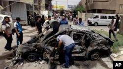 Warga Baghdad mengelilingi sebuah mobil yang hancur akibat ledakan bom (Foto: dok). Dua serangan bunuh diri terpisah di kota Mosul menewaskan dua polisi dan satu tentara serta melukai tujuh lainnya termasuk dua warga sipil, Senin (24/6).