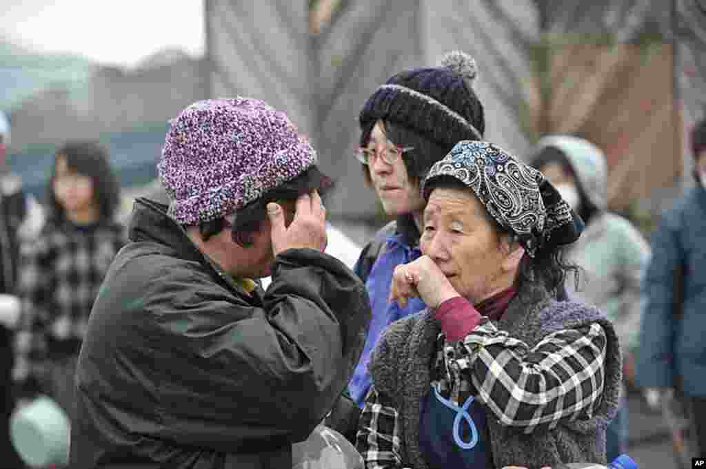 Two women cry with one another while waiting for water at a distribution point in Ofunato five days after the devastating earthquake and ensuing tsunami, March 16, 2011. (AFP)