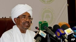 FILE - President Omar al-Bashir called for Sudanese national reconciliation before an audience that included his arch-rival, the religious and Islamist political leader Dr. Hassan al-Turabi, Jan. 28, 2014.
