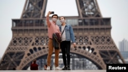 People take a selfie in front of the Eiffel Tower in 2020. A new French dictionary came out, supporting the way the language is spoken outside of France for the first time. (REUTERS/Gonzalo Fuentes)