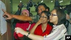 Thân nhân kiểm tra danh sách các hành khách trên chuyến bay bị mất tích, tại sân bay Halim Perdanakusuma ở Jakarta, Indonesia, 9/5/2012