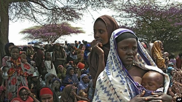 Somalis displaced by drought wait to receive food in their makeshift camp in Mogadishu, July 23, 2011