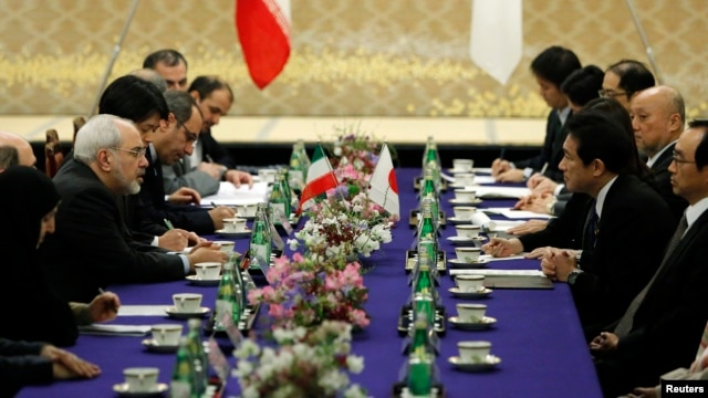 Iran's Foreign Minister Mohammad Javad Zarif (2nd L) speaks with his Japanese counterpart Fumio Kishida (2nd R) at a meeting in Tokyo, March 5, 2014, as Japan paid Iran $450 million owed for oil imports.