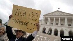 Seorang demonstran mengacungkan poster dalam protes menentang eutanasia di depan parlemen Portugal, di Lisbon, Portugal, 29 Mei 2018. (Foto: Reuters)
